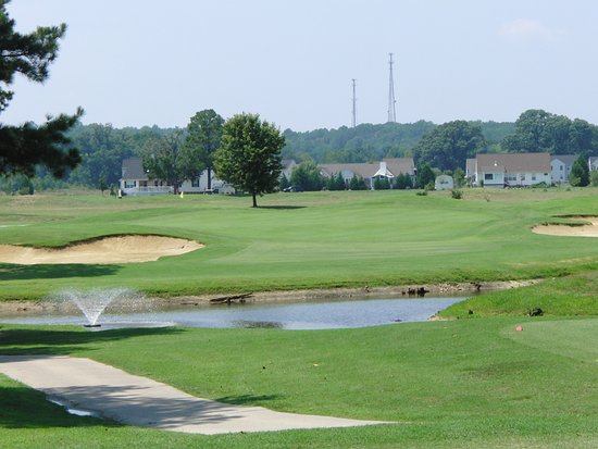 Tappahannock, VA: Signature Par 3 7th featuring water, a multi-tiered green and large surrounding bunkers