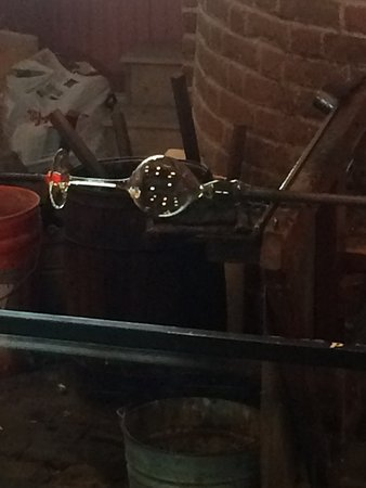 Sandwich, MA: Shaping a wine glass by blowing the glass