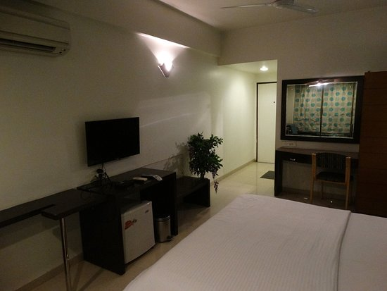 Hotel Laksh Residency: A wall-mounted TV, and desk area
