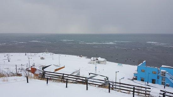 Soya Misaki: 高台の宗谷岬公園から見た、最北端の地の碑と海。青い建物がお土産屋さん