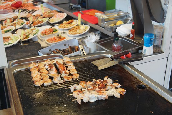 there are many food vendors cooking food for you to eat right there at the fish
