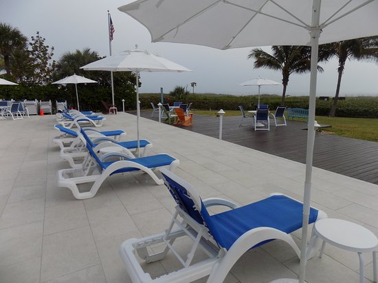 open sundeck with lounge chairs patio tables chairs and grills