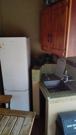 Skukuza Rest Camp : Przed wejściem lodówka, umywalka, szklanki i inne przybory oraz stolik z krzesłami.