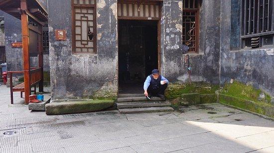 Hongjiang, Chiny: Cleaing teeth; life goes on around us.