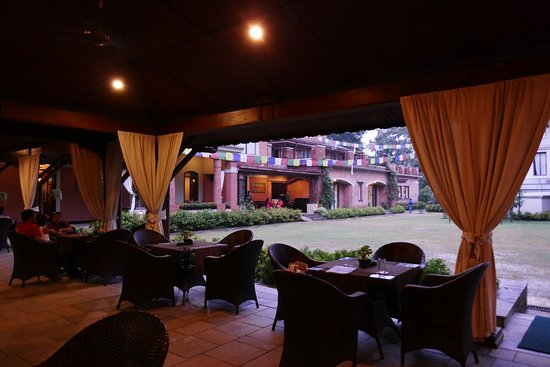 Gokarna Forest Resort: An outdoor dining area adjacent to a large bar and indoor area.