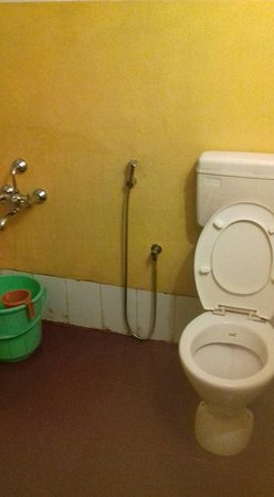Devala, India: Basic bathroom with mud walls but has a tiled floor and maintained clean