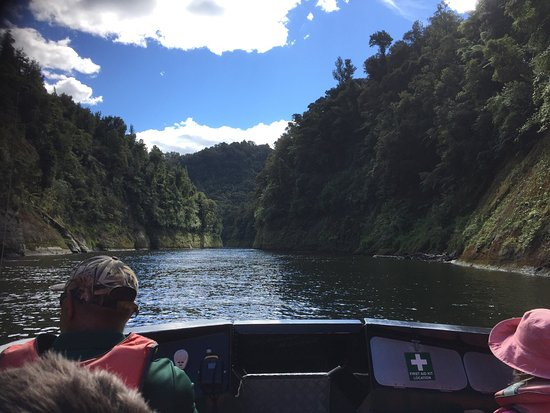 Whanganui River Adventures: Thomas our guide, taking us down the river, mountain bikes secured on back of jet boat