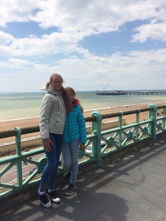 Ett vackert gjutjärnsräcke kantar trottoaren hela vägen utmed Brighton beach - i bakgrunden pire