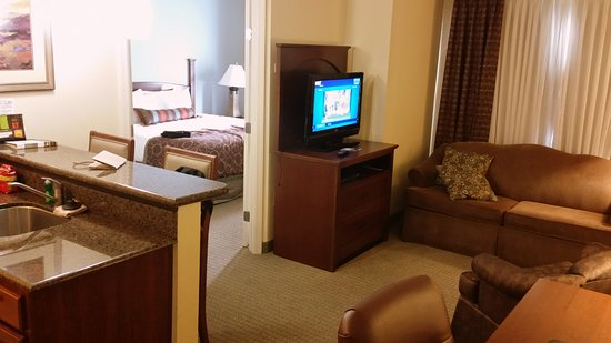 Staybridge Suites Lafayette-Airport: Small sitting area, bedroom though door. Desk with back to the TV.
