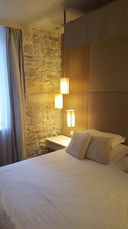 Art Hotel Kalelarga: Literie très confortable et mur en pierre magnifique.