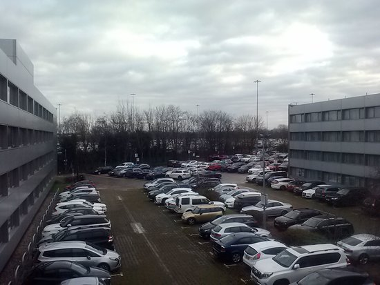 Crowne Plaza Manchester Airport: Parking Lot with Runway behind Trees