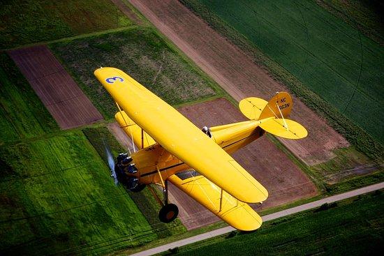 Brodhead, WI: Waco Biplane flying over Wisconsin farmland.