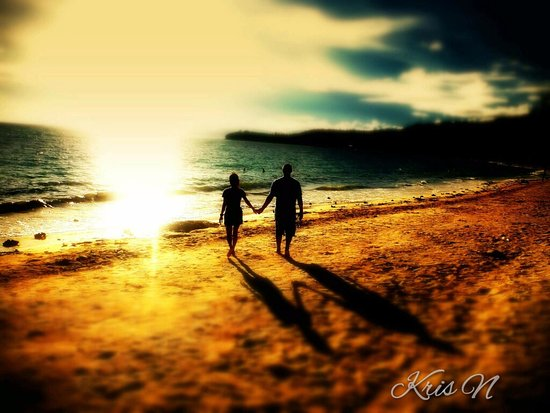 Glan, Philippines: Walking hand in hand along the shore of Gumasa during sunset