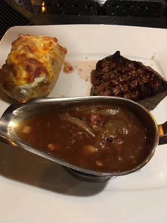Ramstein-Miesenbach, Germany: Lady's steak with baked potato, Cesar's salad & onion gravy - fantastic!