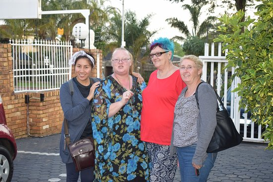 Krugersdorp, South Africa: Our hostess in red with our family, with the security gate behind.