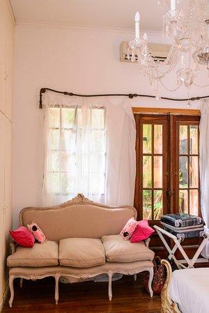 Tesorito Bed & Breakfast: cómodo sillón de época en el cuarto principal con vista al patio
