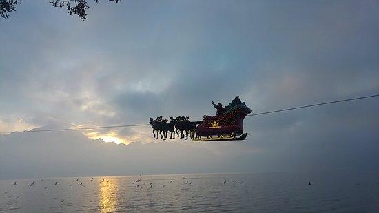 Mercato di Natale di Montreux (Montreux Noel) : Papa Nöel sobre volando el lago al atardecer.