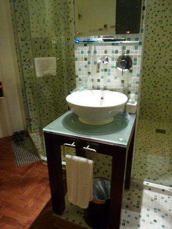 Hotel 1929: shower and toilet inside glass enclosure, sink in room