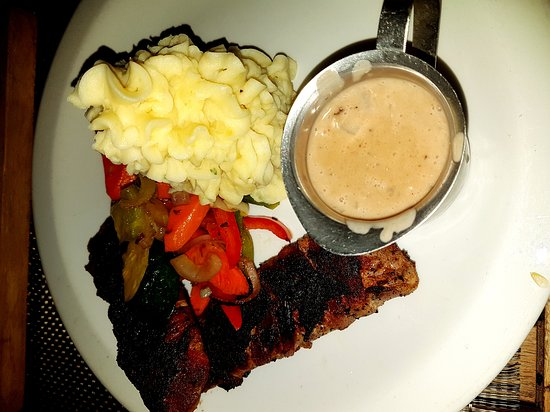Worthing, Barbados: Bacon wrapped pork loin with mashed potatoes, roasted vegetables and wine gravy. Yum!