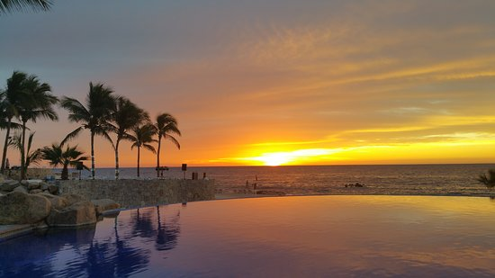 early morning sunrise over infinity pool overlooking the ocean