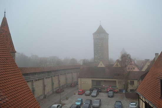 Prinzhotel Rothenburg: Close view is of parking for ther business, but you see the old city wall beyond. Foggy day.