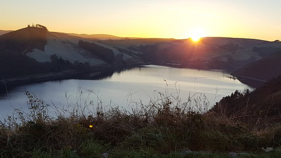 Llanidloes, UK: sunset over the reservoir (November), light snow on the hills.
