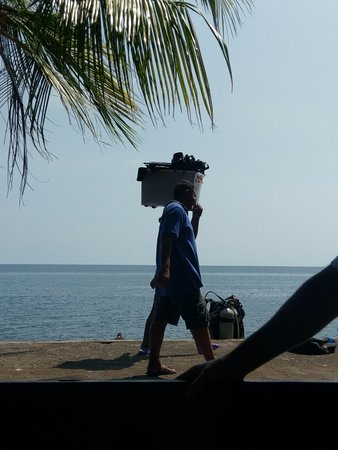 Tulamben, Indonésia: hard worker lady carrying diving equipment.