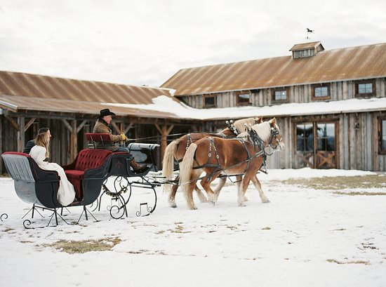 The Ranch at Rock Creek: Newlyweds enjoy a sleigh ride to their reception in the Buckle Barn.