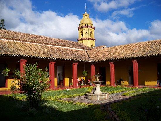 Ocana, โคลอมเบีย: Plaza-jardín interior del Complejo con la vista posterior de la Iglesia de San Francisco de Asis