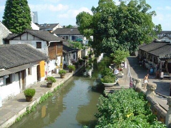 Shaoxing, China: 古くからの運河のそばの橋。 運河の側では、夏でも、練炭を燃やして、お湯を沸かしています。 昔からの姿でしょうね。  橋を渡ってきた女性と目が合いました。 振り返って写真を撮りました。