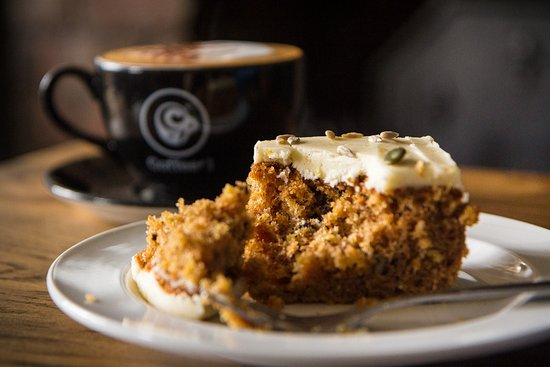 Clevedon, UK: Our scrumptious carrot cake with a perfectly crafted cappuccino