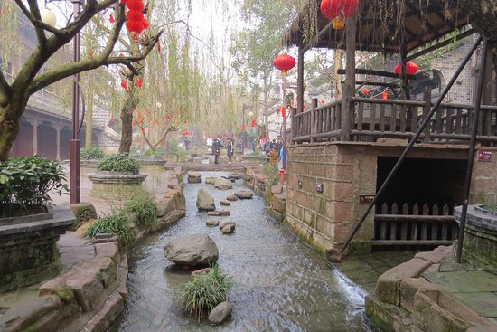 Leshan, Κίνα: 因為快過農曆年了,古鎮街道的佈置有了年味。街道兩邊有各式民宿、小吃、現宰的羊肉作烤肉串、現捶的糖、現燙的ㄧ串麵(看著年輕的師傅隨著音樂跳著很有活力,彷彿麵條也Q彈)、打陀螺、手工剁辣等。推薦去