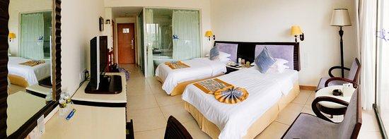 Landscape Beach Hotel Sanya: У ванной комнаты стеклянная стенка, которую можно зашторить. Есть душевая кабина и ванная.