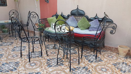 Hotel Sindi Sud: Terrace dining with birds sitting on chairs.