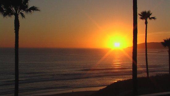 Kon Tiki Inn: Sunset thru the palms to the north from the inn!!