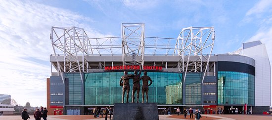 Stretford, UK: Old Trafford featuring the Trinity statue outside of the East Stand