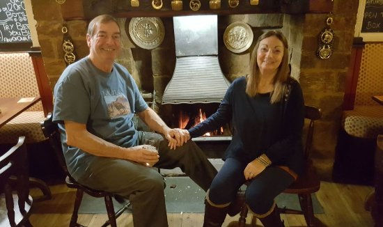 Hook Norton, UK: Enjoying a great pint of the locally brewed beer by a roaring log fire