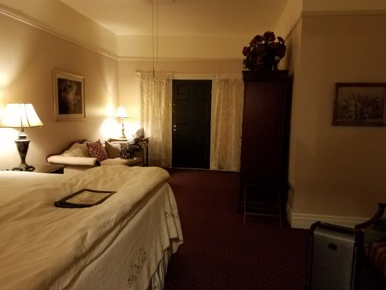 Gruene Homestead Inn: View of room from bathroom - two chairs and table to the right of bed
