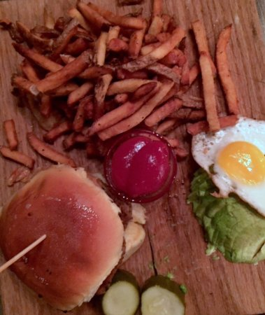 Atlantic Beach, NY: A cutting board serves as your plate of a turkey burger, pickle, fries, avocado and fried egg