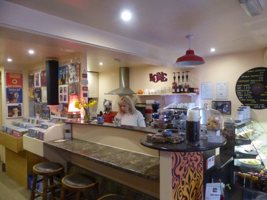 Muse Music and Love Cafe: Val in the cafe half,selection of home baked cakes on the counter