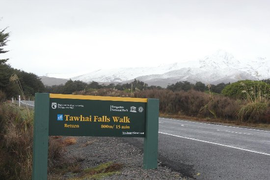 National Park Village, Νέα Ζηλανδία: 滝への入口にある標識と雪で白くなり始めたトンガリロ山。