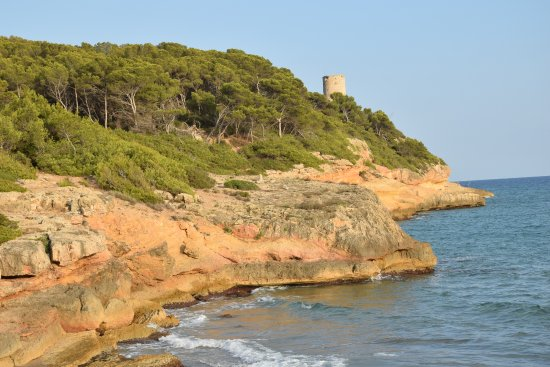 Torre De La Mora: Aussicht von einem kleinen Strand zum Turm.