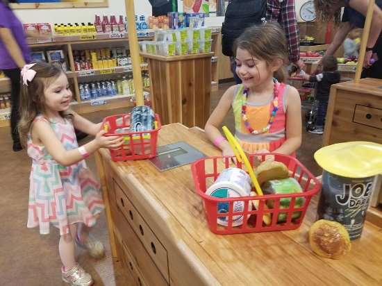Pretend City Children's Museum: Cashier and customer role playing in the miniature Trader Joe's