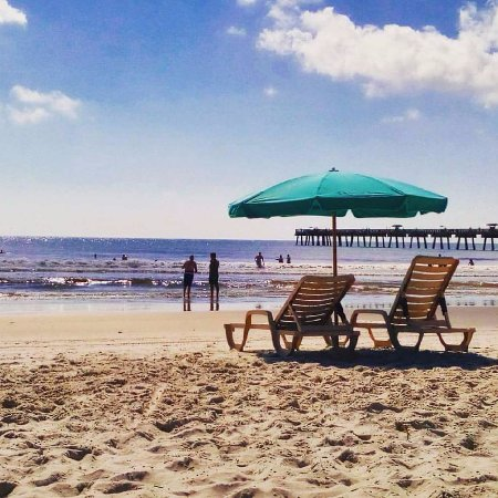 Relax in a chaise lounge under a cool umbrella near the Jacksonville Beach Pier and the Casa Mar