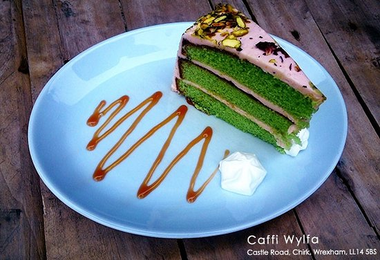 Chirk, UK: Pistachio rose cake look served with cream. A very popular choice at Caffi Wylfa.