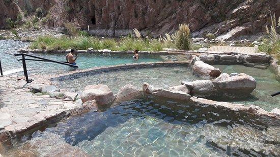 Termas Cacheuta - Terma Spa Full Day: desde la pileta de 43 grados las aguas van decantando en las piletas inferiores, de fondo el río