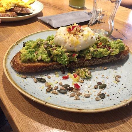 Epping, UK: Smashed avocado and poached egg on sourdough