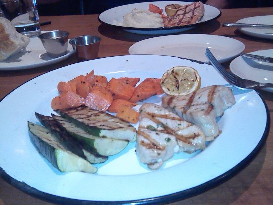 Corona, Καλιφόρνια: My Charbroiled Ono with glazed carrots and grilled zucchini. My husband's salmon in rear.