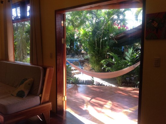 Tico Adventure Lodge: Double doors opening to our porch with table, hammock and pool. So comfortable and Tico!