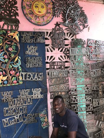 Village Artistique de Noailles: An artist poses with some of his work